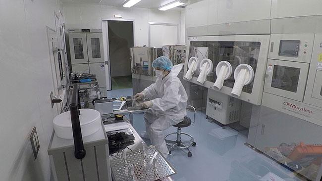 無塵衣着用で、クリーンルームでの作業風景です。温度測定のための治具を設置しています。
